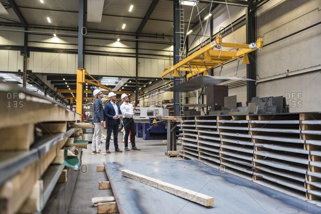 Three men wearing hard hats standing on factory shop floor