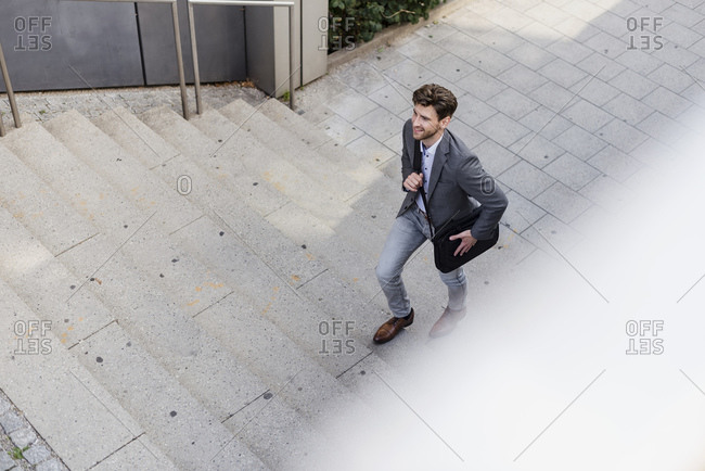 Smiling businessman with crossbody bag walking upstairs
