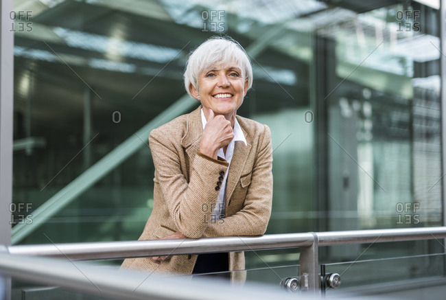 Portrait of smiling senior businesswoman leaning on railing in the city