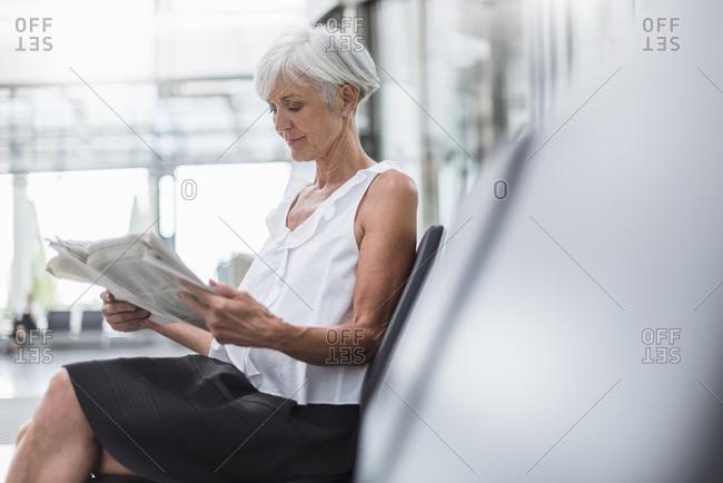 Senior woman sitting in waiting area reading newspaper
