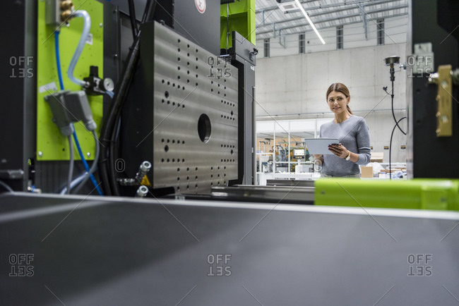 Businesswoman in high tech company controlling manufacturing machines- using digital tablet