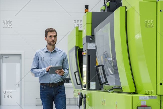 Businessman in high tech company controlling manufacturing machines- using digital tablet