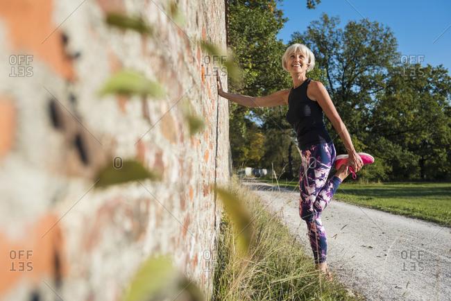 Smiling sportive senior woman stretching at a brick wall