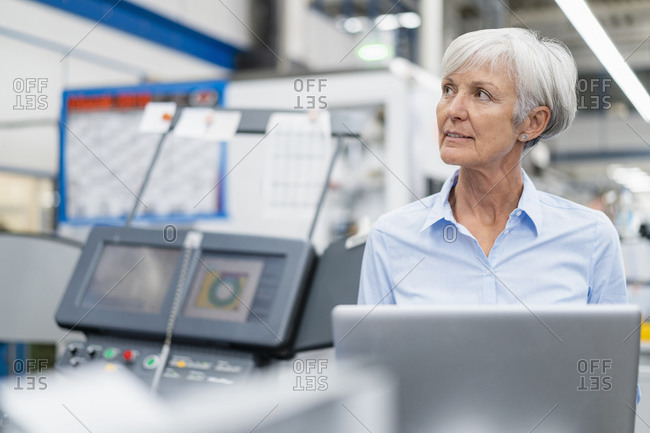 Senior businesswoman with laptop in a factory looking around
