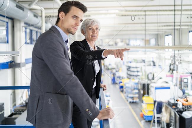 Senior businesswoman and businessman on upper floor in factory overlooking shop floor