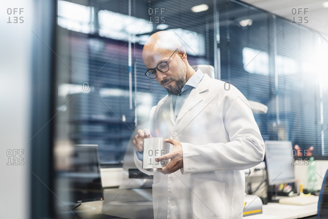 Technician wearing lab coat examining workpiece