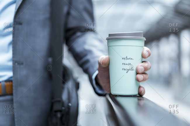 Close-up of businessman holding recyclable takeaway coffee cup
