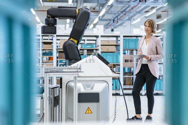 Businesswoman with tablet in a modern factory hall looking at robot