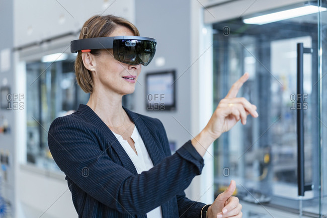 Businesswoman wearing AR glasses in a modern factory