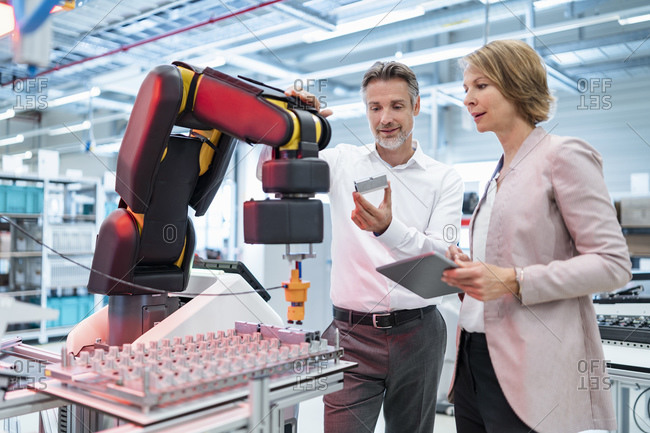 Businessman and businesswoman talking in a modern factory hall