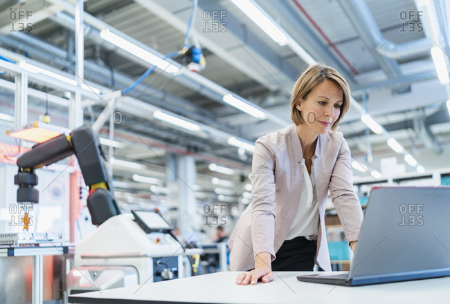 Businesswoman in a modern factory hall using laptop