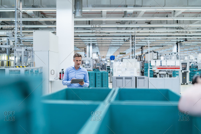 Businessman with tablet in a factory hall