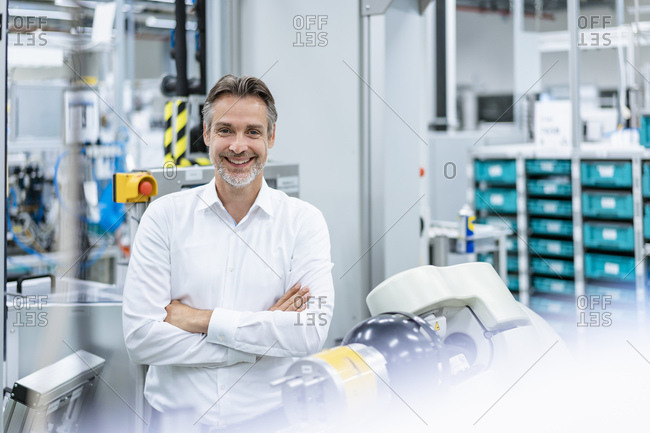 Portrait of happy businessman at assembly robot in a factory