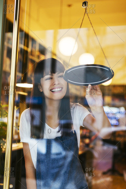 Happy woman turning sign in window of a store