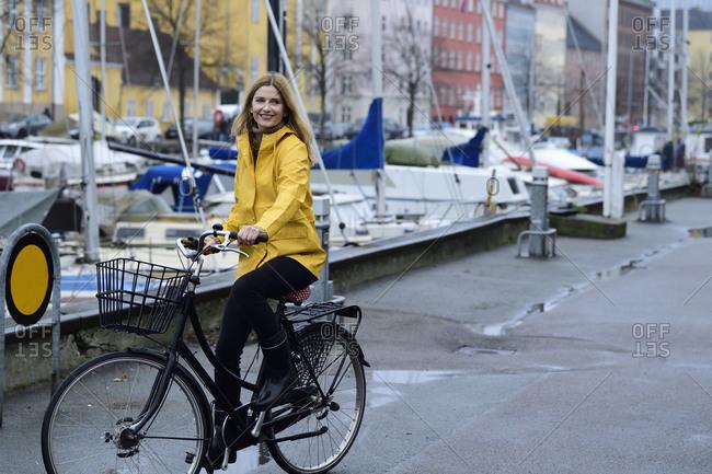 Denmark- Copenhagen- happy woman riding bicycle at city harbor in rainy weather
