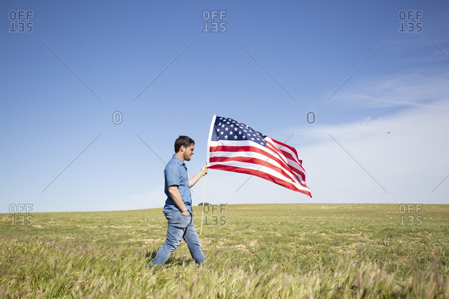 Man with American flag walking on field in remote landscape