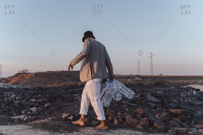 Young man holding empty plastic bottles walking in barren land