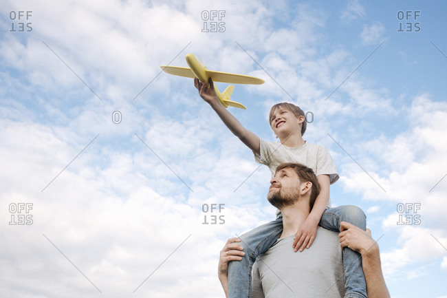 Man carrying son on shoulders playing with toy airplane against sky