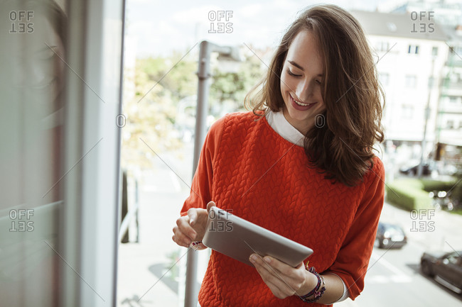 Smiling young woman holding tablet on balcony