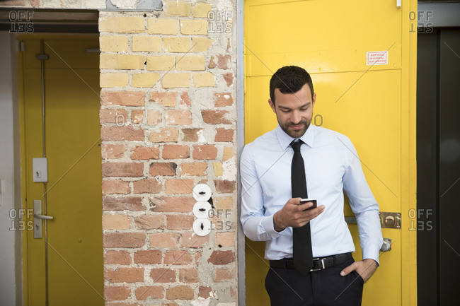 Businessman leaning in front of elevator using smartphone