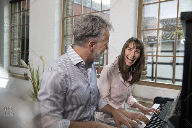 Mature couple having fun at home- playing the piano
