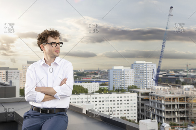 Germany- Berlin- content businessman on roof terrace looking at view