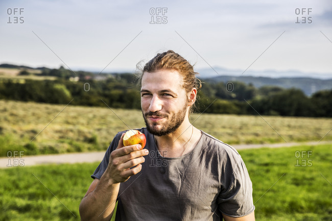 Young man eating an apple in rural landscape