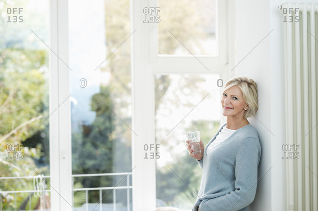 Portrait of senior woman with glass of water in front of window