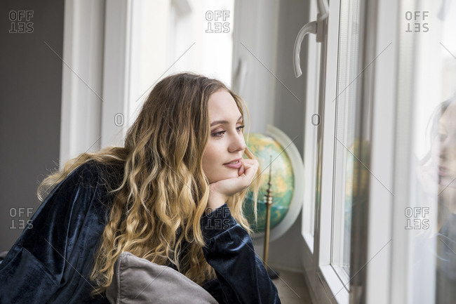 Portrait of daydreaming young woman looking through window