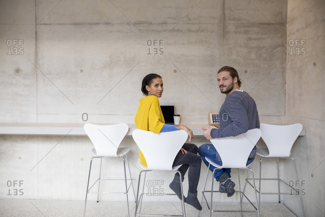 Young man and woman using mobile devices in concrete room