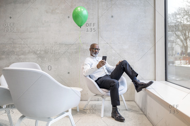 Mature businessman with green balloon sitting on armchair looking at cell phone