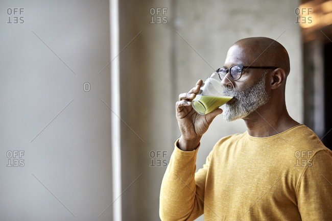 Mature businessman in office drinking a smoothie