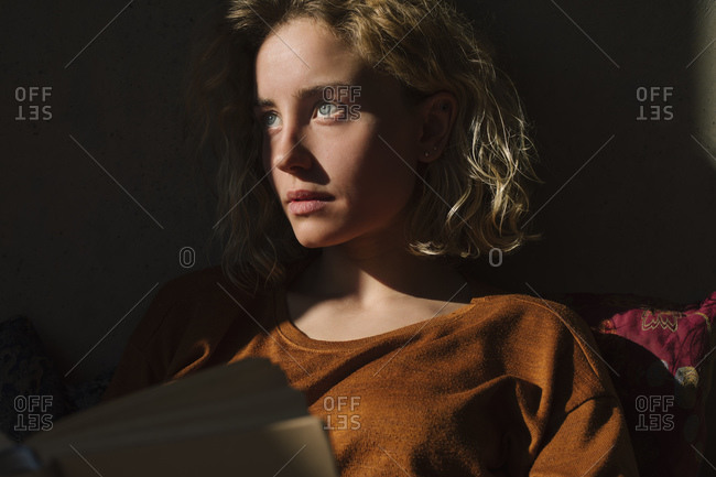 Portrait of pensive student with book looking at distance