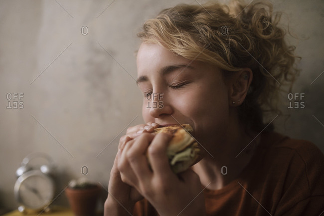 Portrait of young woman eating Hamburger