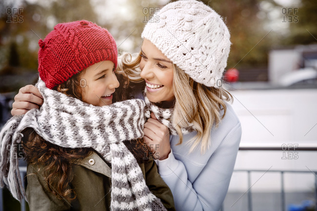 Happy mother and her little daughter wearing woolly hats and knitted scarf