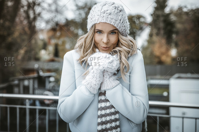Portrait of smiling woman wearing woolly hat- gloves and scarf