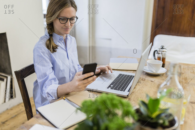 Woman using cell phone and laptop on wooden desk at home