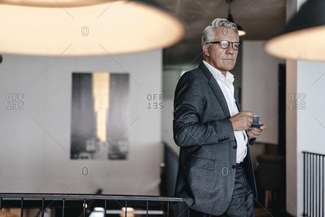 Senior businessman drinking coffee- looking worried