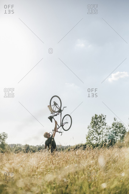 Young man lifting up his bike