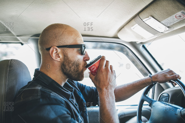 Young man with sunglasses and beard on a road trip with takeaway drink