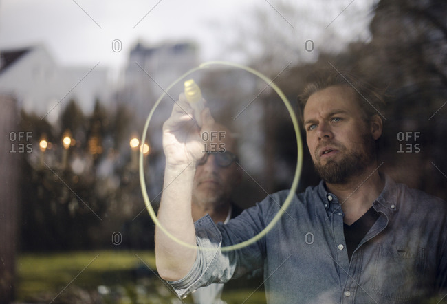 Mature man drawing a circle on window pane- senior man watching