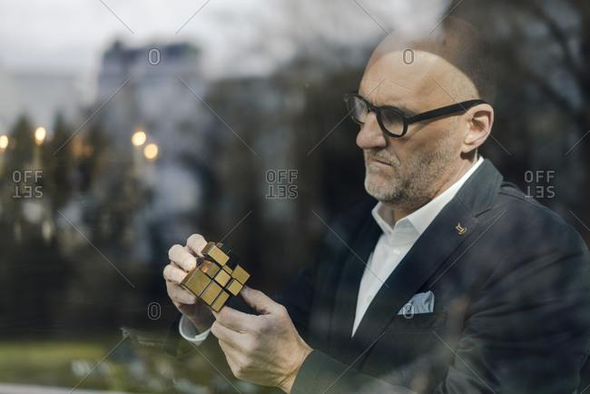 Senior businessman putting together puzzle cube
