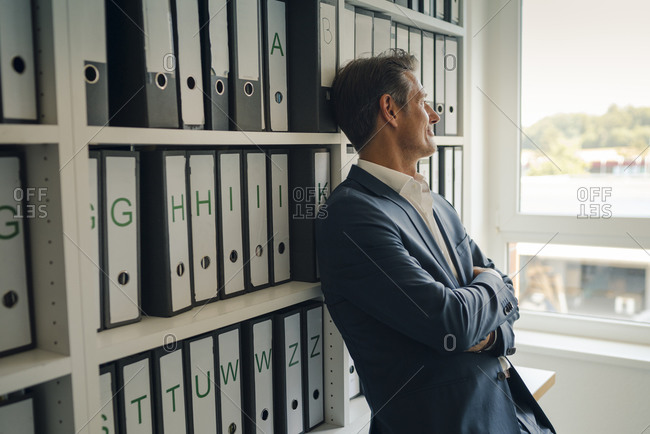 Businessman in company archive- leaning against shelf with files