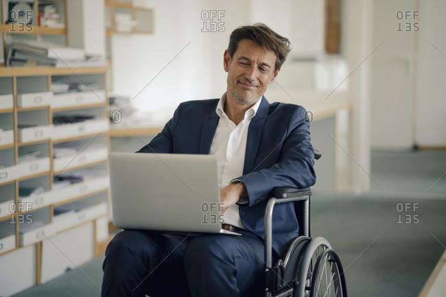 Businessman in wheelchair- using laptop in office