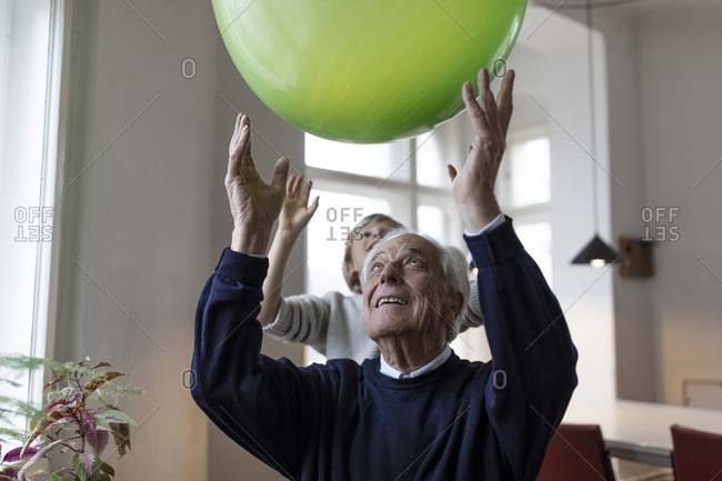 Happy grandfather and grandson playing with balloon at home
