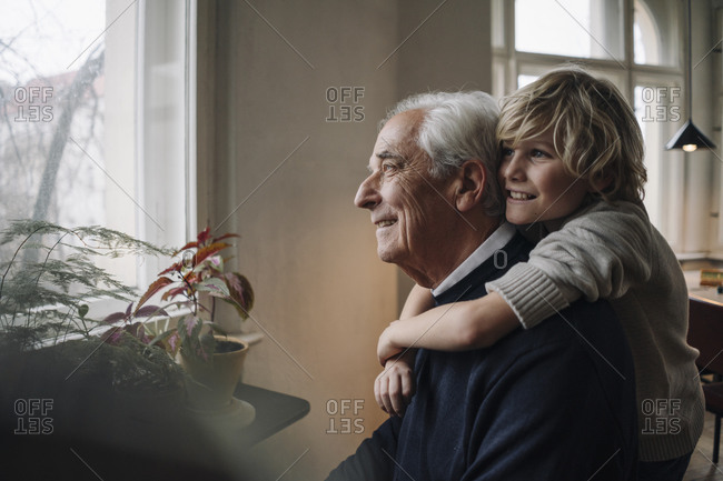 Happy grandson embracing grandfather at home