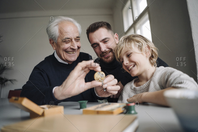 Happy watchmaker showing clockwork to young man and boy
