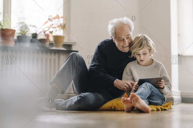 Grandfather and grandson sitting on the floor at home using a tablet