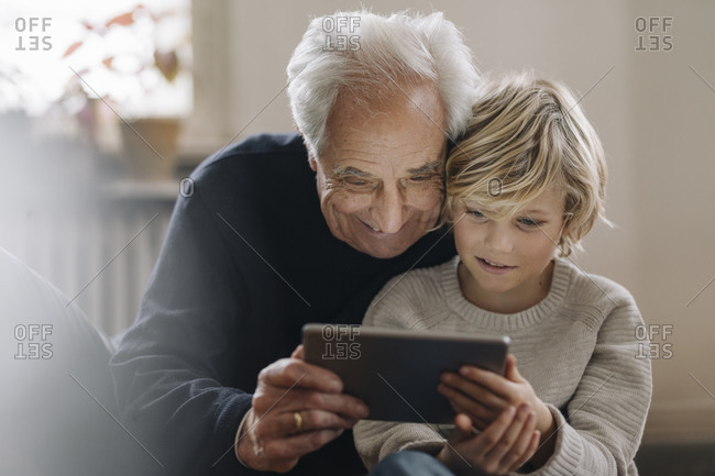 Grandfather and grandson using a tablet at home