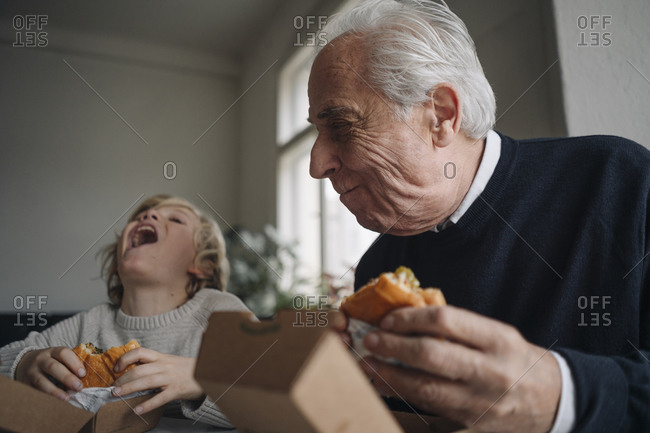 Happy grandfather and grandson eating burger together at home